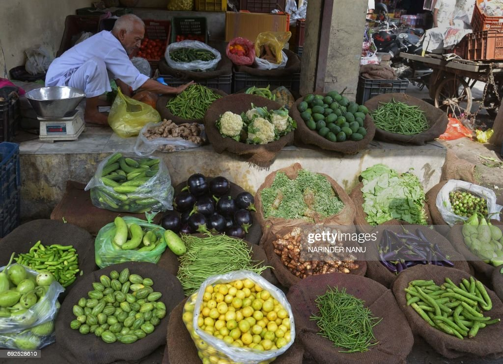 Indian vendor Amir Chand displays vegetables for sale at a roadside shop in Amritsar on June 5 2017 / AFP PHOTO / NARINDER NANU
