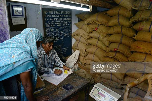 Indian vendor Brij Kishore processes the ration card of an Indian woman at his Fair Price Shop a government food dispensary in the northern district...