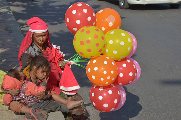 TOPSHOT Indian vendor Geeta sits on the side of the road with her two children as she sells Santa Claus hats and balloons at the roadside in Amritsar.