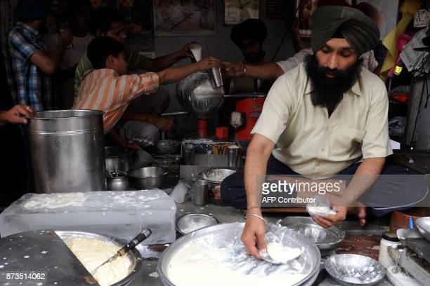 Indian vendor Gurinder Singh makes lassi at The Punjabi Lassi Stall in Amritsar on April 16 2010 Lassi is made by blending yoghurt with water milk...