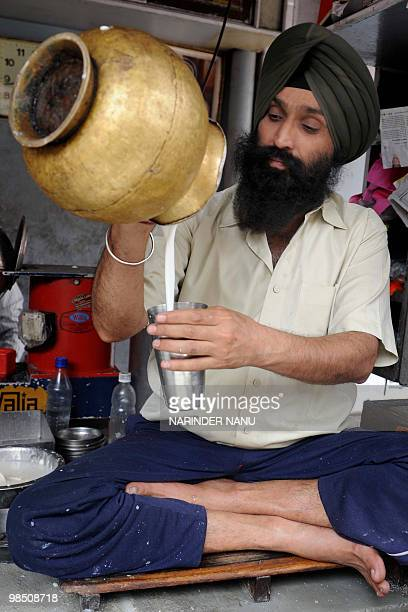 Indian vendor Gurinder Singh makes lassi at The Punjabi Lassi Stall in Amritsar on April 16, 2010. Lassi is made by blending yoghurt with water, milk...