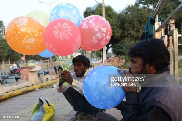 Indian vendor Mukesh blows balloons for sell to commuters along a road in Amritsar on December 2 2017 / AFP PHOTO / NARINDER NANU