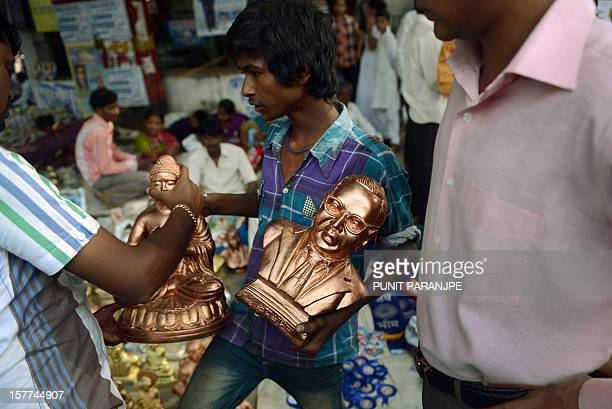A Indian vendor sells statues of Bhimrao Ambedkar and Lord Gautam Buddha on Ambedkar's 56th death anniversary near the historic Chaitya Bhoomi...