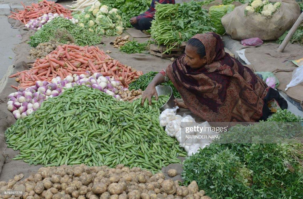 Indian vendor Shakuntala displays vegetables for sale at a roadside in Amritsar on November 26 2017 / AFP PHOTO / NARINDER NANU
