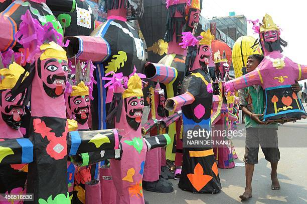 A Indian vendor waits for customers as he sells effigies of the Hindu demon King Ravana at the roadside in Amritsar on October 2 2014 on the eve of...