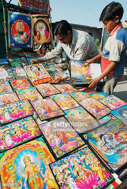 Indian vendors Nikku and Raju adjust pictures of Hindu Gods Laxmi and Ganesh at their road side stall, 27 October 2005 in Amritsar, in India's...