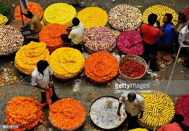 Indian vendors sell flowers for the celebration of the festival of Pongal at the main wholesale market in Bangalore on January 14 2010 Pongal is a...
