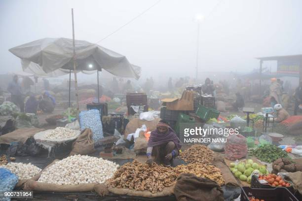 Indian vendors sell vegetables at a wholesale vegetable market on the outskirts of Amritsar on January 3 2018 / AFP PHOTO / NARINDER NANU
