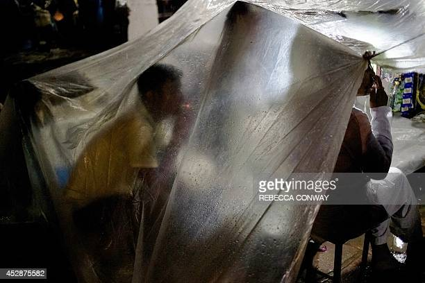Indian vendors smoke cigarettes as they sit under a plastic sheet in heavy rain while waiting for customers during Chand Raat celebrations at a...