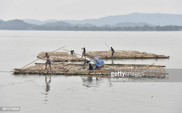 Indian vendors steer a bamboo pontoon along the Brahmaputra River in Guwahati on June 1 2017 One of Asia's longest rivers the 2900km Brahmaputra...