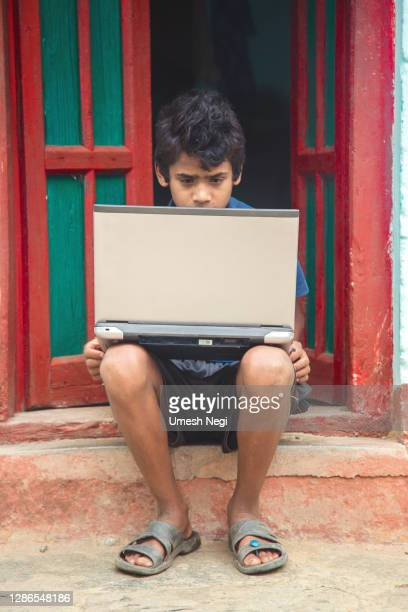 indian village boy operating laptop computer system seating at home corridor - borough district type stock pictures, royalty-free photos & images