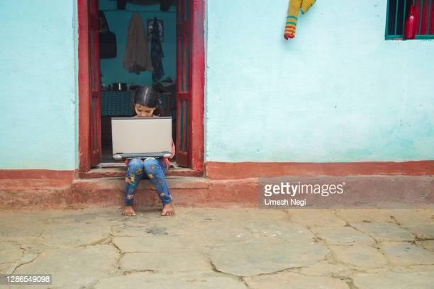 indisk by flicka som driver laptop datorsystem sittplatser hemma korridor - fattigdom bildbanksfoton och bilder