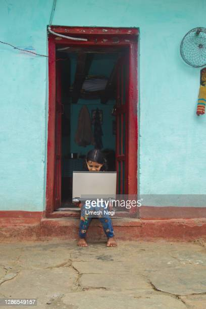 indian village girl operating laptop computer system seating at home corridor - borough district type stock pictures, royalty-free photos & images