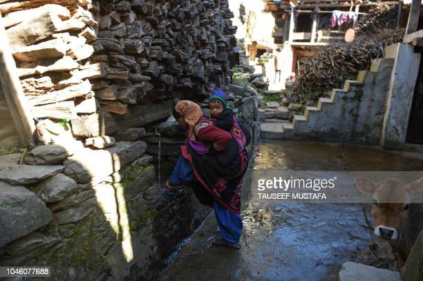 Indian villager drinks water as riders compete nearby in the 14th edition of the Hero MTB Himalaya mountain bike race in the northern Indian state of...
