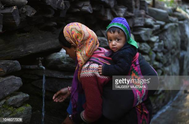 Indian villager drinks water with a baby as riders compete in the 14th edition of the Hero MTB Himalaya mountain bike race in the northern Indian...