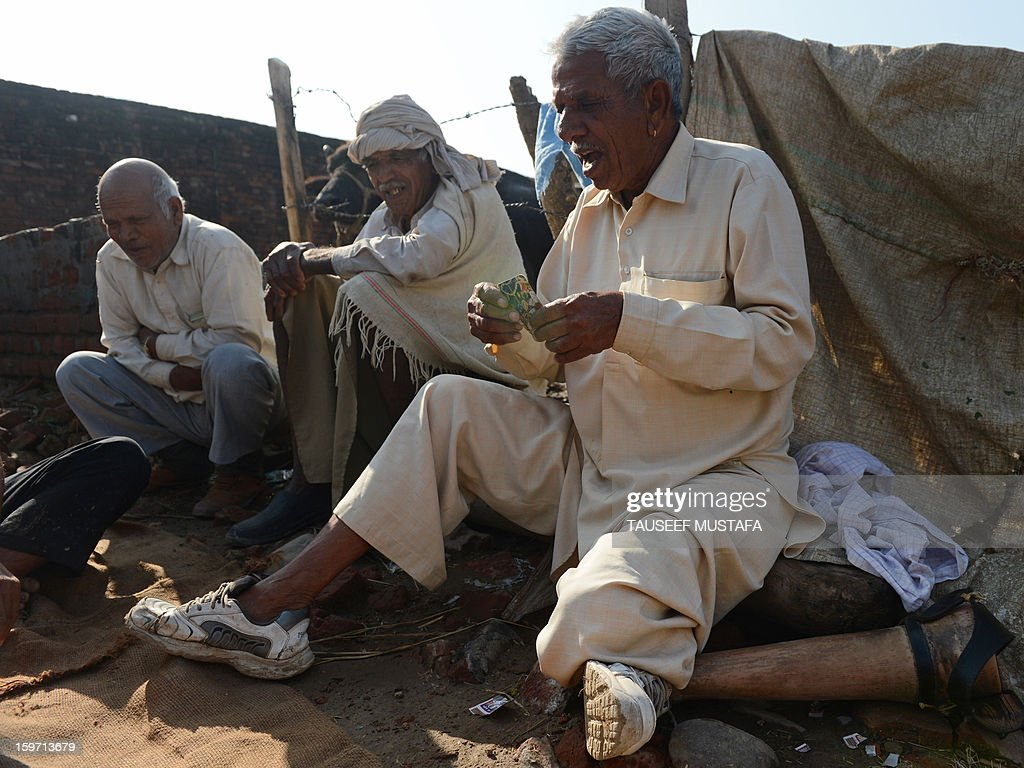 Indian villager Shama (R), who lost his leg in a landmine blast following the 1972 Indo-Pakistan war, plays a game of cards with fellow villagers near the India-Pakistan border in Gharana, some 35 kms southwest of Jammu, on January 19, 2013. On both sides of the de facto border in Kashmir, villagers living on one of the world's most dangerous flashpoints have special reason to fear the return of tension between India and Pakistan. The spike in cross-border firing in Kashmir -- a region claimed wholly by both India and Pakistan -- has seen five soldiers killed in recent days and threatened to unravel a fragile peace process that had begun to make progress. AFP PHOTO/Tauseef MUSTAFA