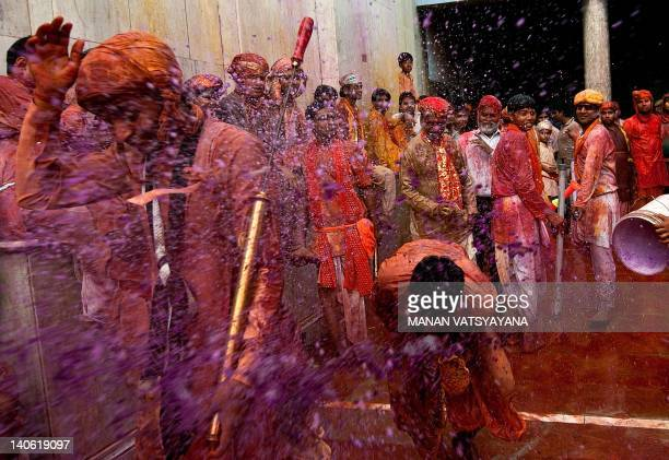 Indian villagers are sprayed with coloured water during the Lathmar Holi festival at the Nandji Temple in Nandgaon some 120 kms from New Delhi on...