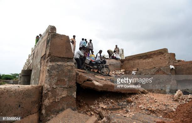 Indian villagers assist a motorcyclist to cross a flooddamaged bridge in the village of Aya in Surendranagar District some 150kms from Ahmedabad on...