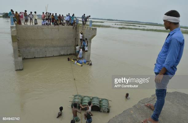 TOPSHOT Indian villagers attempt to cross flood waters with the help of rope and empty canisters next to a washed away portion of a bridge at Palsa...