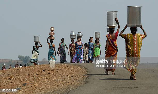 Indian villagers carry containers home after collecting supplies of potable water from a well following a tanker's daily delivery in Shahapur, some...