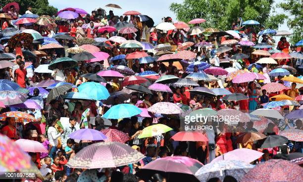 TOPSHOT Indian villagers carry umbrellas at the Behdienkhlam festival in Tuber village in the northeastern state of Meghalaya on July 19 2018...