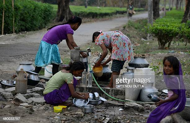 Indian villagers collect drinking water from a tap at the Dagapur Tea garden on World Water Day on the ouskirts of Siliguri on March 22 2014 World...
