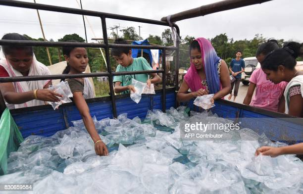 Indian villagers collect water pouches in a flood affected area of Lakhimpur district some 380km from Guwahati in the northeastern state of Assam on...
