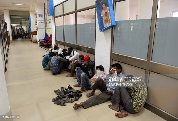 Indian villagers from Anand district of western India's Gujarat state hide their faces at the forensic department of a hospital in Ahmedabad on March...
