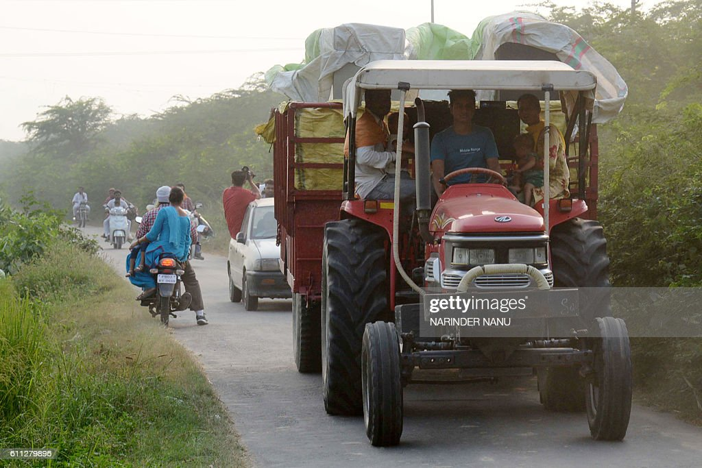 Indian villagers from the IndiaPakistan border area ride on a tractor as they evacuate from a border village near Dauke about 40 kms from Amritsar on.