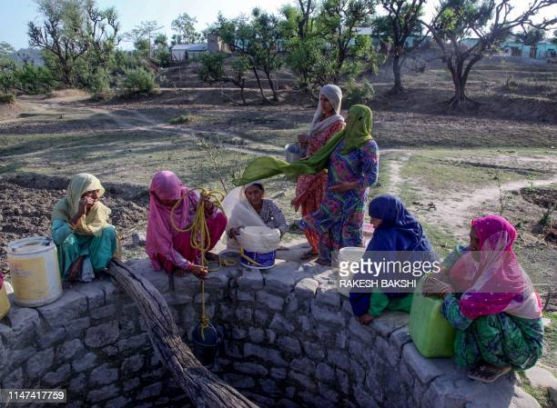 Indian villagers gather near a well running dry to collect drinking water at Padal village of the district of Samba, some 45 km from Jammu, on June...