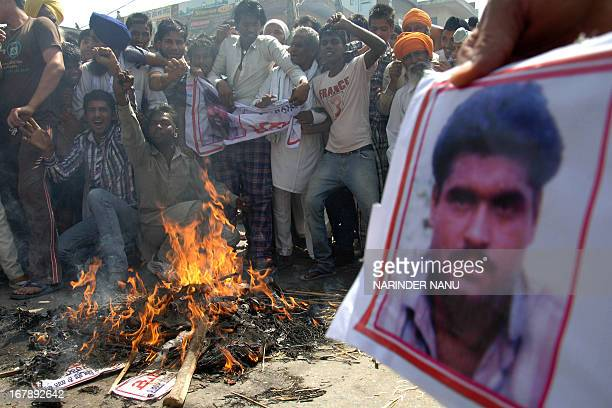 Indian villagers hold a picture of Sarabjit Singh an Indian prisoner killed in Pakistan as they shoutslogans while burning an effigy of Pakistani...