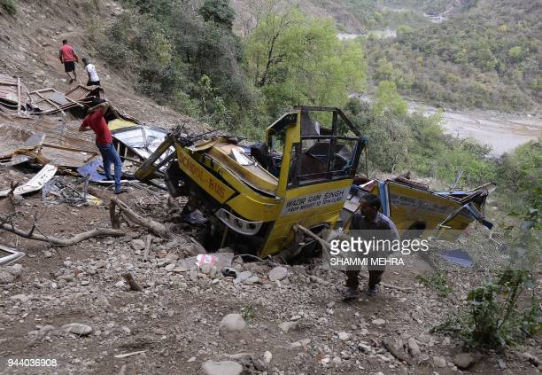 Indian villagers look at a wrecked school bus near Nurpur in Kangra District in India's northwest Himachal Pradesh state on April 10 a day after a...