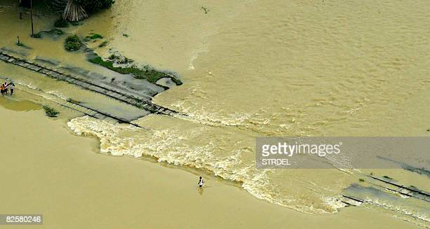 Indian villagers make their way along submerged railway tracks near Madhepura some 250kms northeast of Patna on August 27 2008 Tens of thousands of...