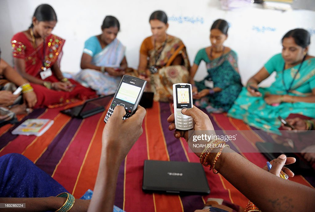 Indian villagers, part of a Self Help Group (SHG) organisation, pose with mobile phones and laptops in Bibinagar village outskirts of Hyderabad on March 7, 2013, on the eve of International Women's day. Members of SHG's make small regular savings contributions over a few months until there is enough capital in the group to begin lending, and they use their mobiles and laptops to record financial transactions. SHG's are seen as instruments for a variety of goals including empowering women, developing leadership abilities among poor people, increasing school enrolments, and improving nutrition and the use of birth control. AFP PHOTO / Noah SEELAM