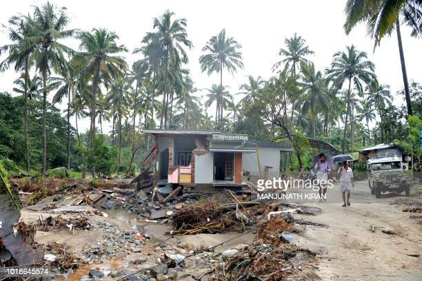 Indian villagers pass next to a house destroyed by a landslide at Kannapanakundu village in Kozhikode district about 422 km north of Trivandrum in...