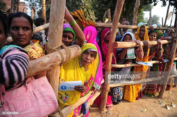 TOPSHOT Indian villagers queue outside a bank as they wait to deposit and exchange 500 and 1000 rupee notes in Hanuman Ganj village on the outskirts...