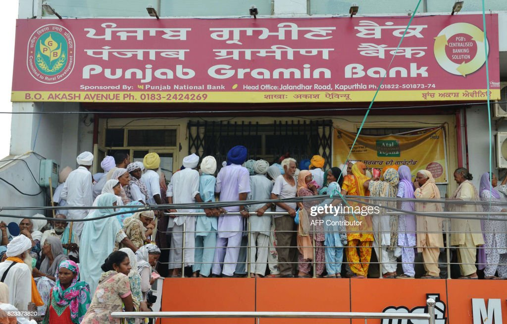 Indian villagers queue to receive their pension some 500 INR outside a bank in Amritsar on July 27 2017 / AFP PHOTO / NARINDER NANU