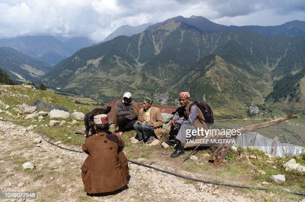 Indian villagers sit as riders compete nearby in the 14th edition of the Hero MTB Himalaya mountain bike race in the northern Indian state of...