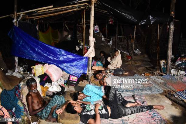 Indian villagers take rest in the open as the cyclone fani destroyed their house in Puri in the eastern Indian state of Odisha on May 11 2019 The...