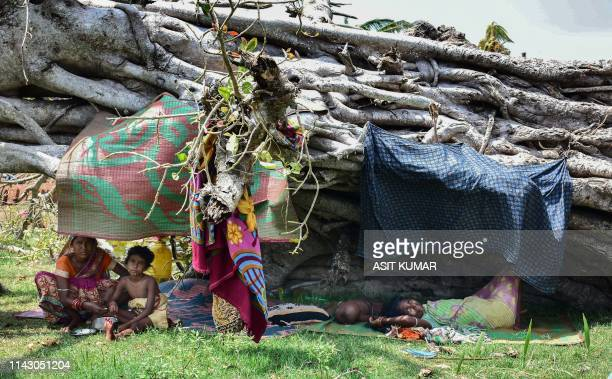 Indian villagers take shelter under an uprooted tree as the cyclone Fani destroyed their house in the Pateli village area of Puri in the eastern...