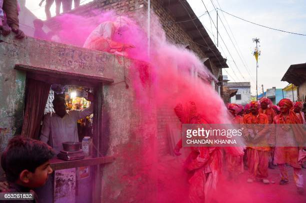 TOPSHOT Indian villagers throw coloured powder over others during Lathmar Holi celebrations in the village of Jaab in Kosi Kalan in Mathura district...