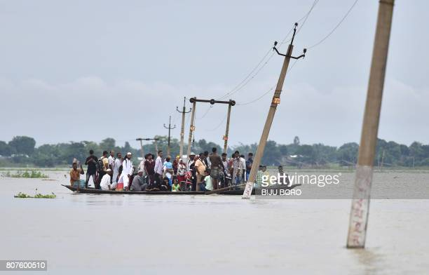 TOPSHOT Indian villagers travel by boat through floodwaters in Balimukh Ashigarh village in Morigoan district in India's northeastern state of Assam...
