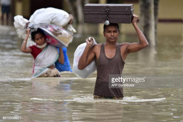 Indian villagers wade through flood waters whilr carrying household items at the flood affected Koliabor village some 186km from Guwahati the capital...
