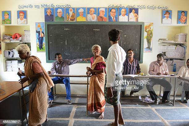 Indian villagers wait to cast their ballot inside a polling station in Bollavaram village in Kurnool district some 250 kilometers from Hyderabad on...