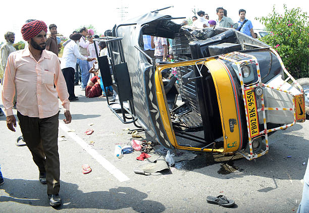 Indian villagers walk past an overturned auto rickshaw near Khasa Village about 20 Km from Amritsar on April 3 2013 Six people were injured when an...