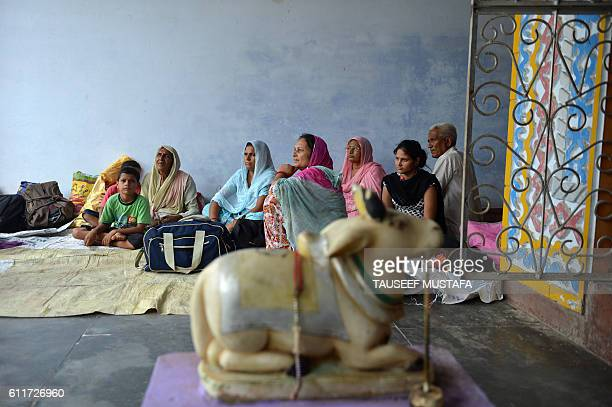 Indian villagers who have migrated from their village close to the border with Pakistan gather in a temple in Khor in Akhnoor Sector west of Jammu on...