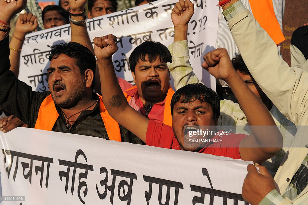 Indian Vishwa Hindu Parishad (VHP) activists shout slogans in front of a statue of Mahatma Gandhi as they protest against the alleged killing of two Indian soldiers by Pakistan in the disputed Kashmir region, in Ahmedabad on January 10, 2013. Pakistan on January 10 accused Indian troops of opening fire and killing a Pakistani soldier, the third deadly cross-border incident in days that threatens to escalate tensions in Kashmir. AFP PHOTO / Sam PANTHAKY