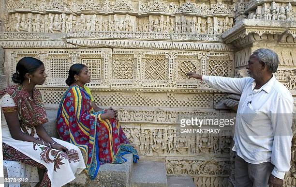 Indian visitors listen as a guide explains a carved relief of The Ran Ki Vav Stepwell at Patan some 120kms from Ahmedabad on November 21 2008 The...