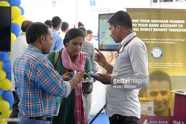 Indian visitors listen to a bank representative regarding digital transactions with an Aadhaar or Unique Identification card during a Digi Dhan Mela...
