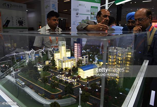 Indian visitors look at a model of a 'smart city' at the Smartcity Expo in New Delhi on May 20 2015 The expo is showcasing sustainable living and...